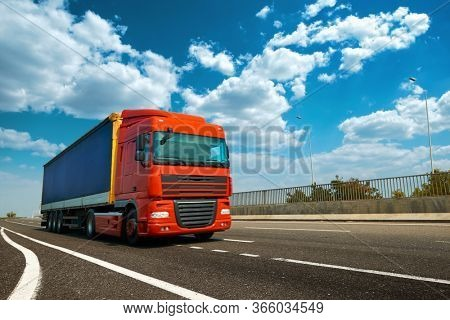 Red truck on highway - business, commercial, cargo transportation concept