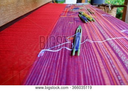 Traditional Weaving Loom With Colorful Cotton Fiber Being Woven Into Clothing.