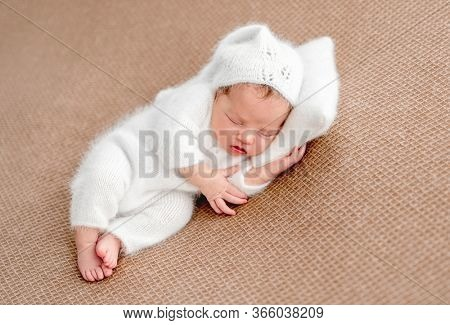 Cute newborn in white suit resting on tiny pillow