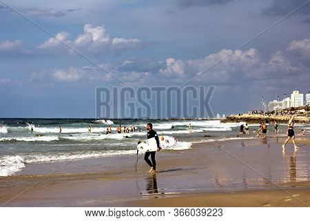 Tel Aviv, Israel, November 2019 - Surfer, A Young Man With A Surfboard Is Walking Near The Sea. Surf