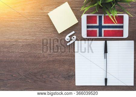 Norwegian Flag Smartphone, Wireless Headphones, Notepad, Green Plant On Brown Desktop, Place For Tex
