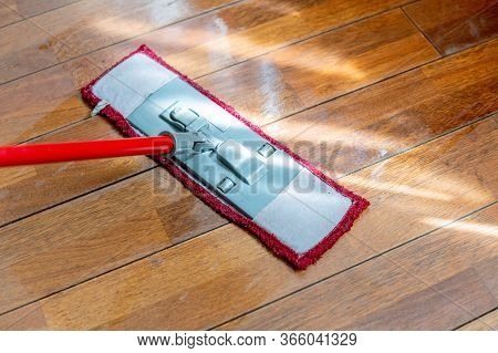 A Mop Washing A Wooden Floor In An Apartment. Concept Of Care For The Cleanliness Of The Apartment.