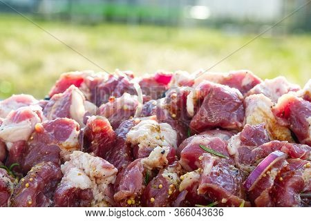 Prepared Marinated With Onions And Herbs Pieces Of Meat For Barbecue. Raw Marinated Skewers On Skewe