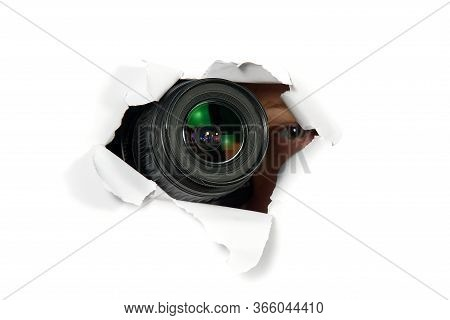 Black Camera With A Telephoto Lens That Looks Out Through A Hole In White Paper. Concept Of Paparazz