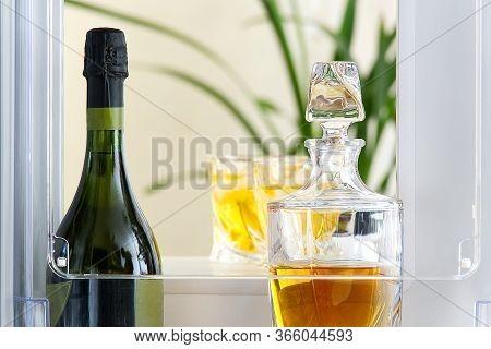 Open Hatch Of A Mini Bar In A Modern Refrigerator. Home Mini Bar In The Fridge. A Glass Carafe Full