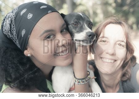 Happy Woman And Daughter Taking Selfie Together. Portrait Of Beautiful Mature Mother, Dog And Her Da
