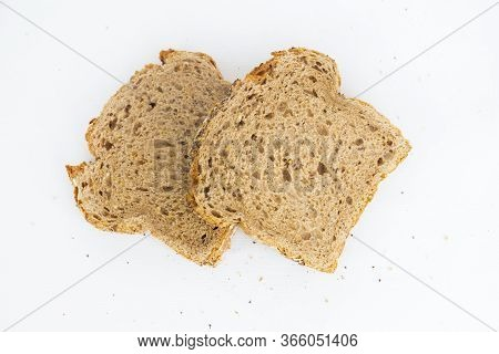 Two Homemade Cutting Slices Of Rye Bread With Oats. Crumbs Laying Around. Soft Brown Loaf Pieces Iso