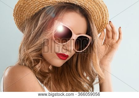 Young Woman Wearing Stylish Sunglasses And Hat On Light Grey Background