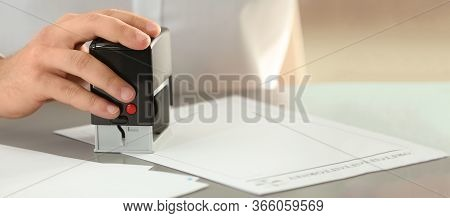 Male Notary Stamping Document At Table, Space For Text. Banner Design