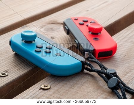 May 2020, Uk: Nintendo Switch Joy Con Controllers Red And Blue Neon Outdoors On Wooden Table
