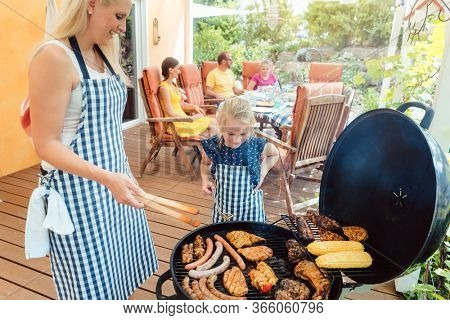 Barbeque party in the garden with mom and her daughter at the grill cooking meat
