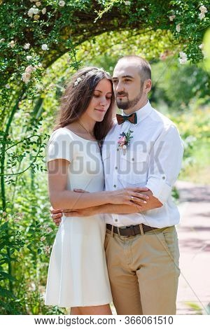 Lovers Newlyweds. Beautiful Couple In Love. Loving Couple In The Garden Among The Flowers. Just Marr