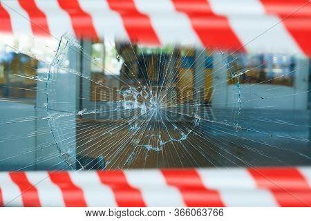 Broken Showcase With Warning Tape. Smashed Window