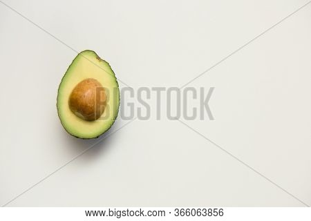 Single Cut Half Of Avocado With Seed. Top View, Closeup, Copy Space. Isolated Object On White Backgr