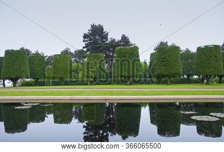 Landscape Design, Neatly Trimmed Trees In Colleville Sur Mer, France. Beautiful Landscaped Garden Wi