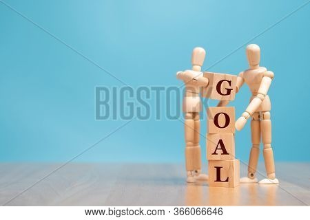 Wooden Puppet Standing And Holding A Wooden Cube For Making A Goal Word. Concept Of Business Managem