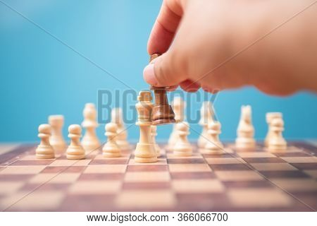 The Hand Of Businessman Holding Brown King Chess And Checkmate Competitor And Win The Games. Concept