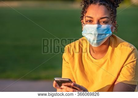 Mixed race biracial African American teenager teen girl young woman wearing a face mask and using mobile cell phone outside during the Coronavirus COVID-19 pandemic