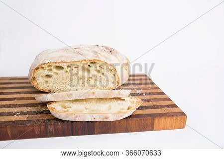 Round Loaf Of Crusty Wheat Bread Cut In Slices And Placed On Chopping Board. Isolated Object On Whit
