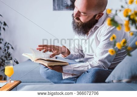Man Reading Book At Home. Domestic Lifestyle. Man Relaxing On Sofa At Home. Hipster Lifestyle. Beard