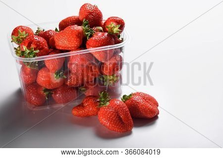 Good Organic Strawberries In A Plastic Box On A White Background. Delivery Of Organic Products. Pack