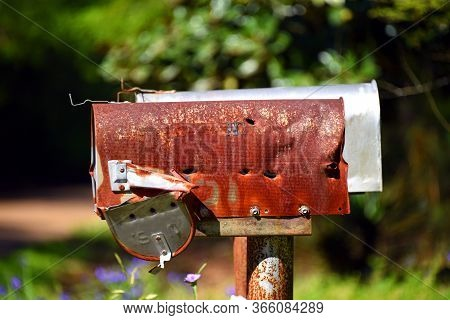 Abandoned Mailbox Has Several Bullet Holes In It.  It Is Rusty, Bent And The Door Is Barely Hanging