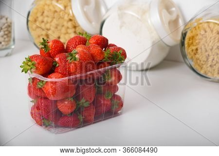 Fresh Organic Strawberries In A Plastic Box In The Kitchen. Delivery Of Organic Products. Packaging