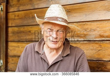 Portrait Of Smiling Elderly Man Wearing A Hat In The His Garden In Springtime.