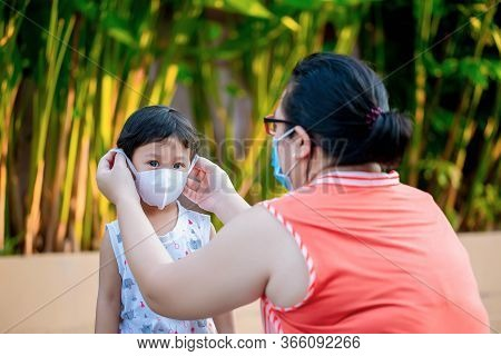 Mother And Child Wear Facemask During Coronavirus And Flu Outbreak. Mother Puts On Her Baby Sterile
