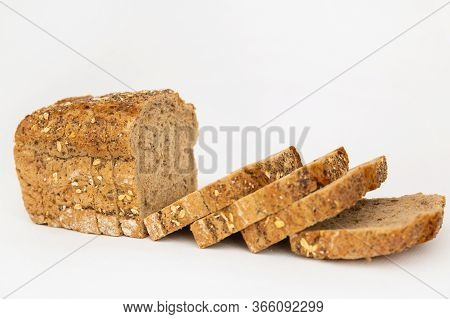 Crusty Sliced Cereal Bread With Oatmeal And Seeds. Pieces Of Brown Loaf Laying Together Isolated On