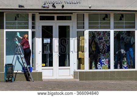Uzhgorod, Ukraine - May 12, 2020: Woman Washes Shop Windows After Weakening The Quarantine Due To Co