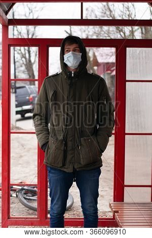 Guy Stands At A Bus Stop In A Medical Disposable Mask. Respiratory Viral Disease Protection Covid-19