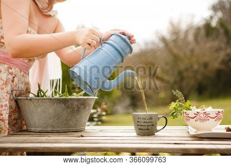 Concept Of Breakfast And Teatime In Open Air. Girl Pours Tea From Vintage Teapot, Pour Into Mug (ins