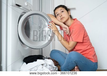 A Girl Loads Dirty Laundry Into A Washing Machine While Sitting On The Floor In An Apartment. Laundr