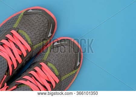 Gray Sneakers With Pink Laces On A Blue Background Top View. Textile Sneakers With Colorful Laces An