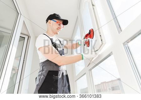 Worker Man Installs Plastic Windows And Doors With Double-glazed White