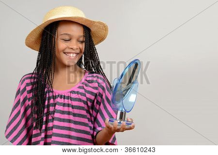 young black girl trying on straw hat
