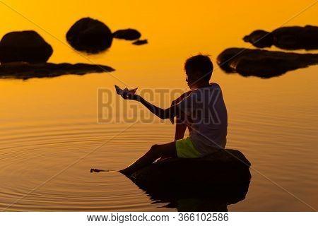 Teen Boy With Origami Ship In Hands. Boy Sitting On Rock Near River. Beautiful Orange Sunset. Origam