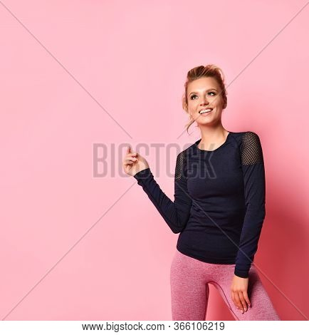 Attractive Happy Young Female In Stylish Workout Clothes Looking Up With Cheerful Smile Bending Her