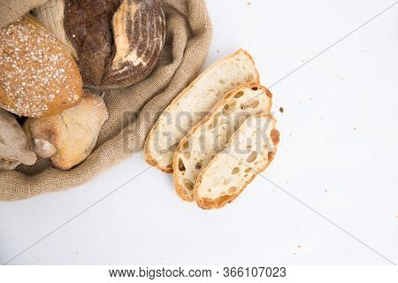 Sliced Bread And Freshly Baked Buns In Rustic Burlap Sack And Wheat Ears. Closeup Shot, Top View, Co