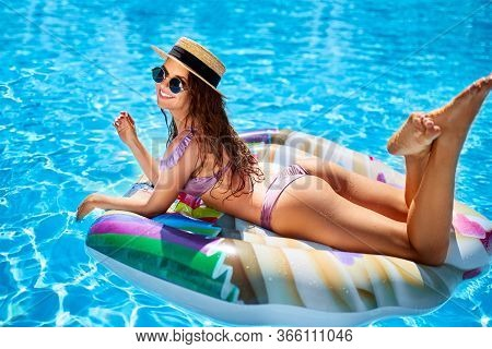 Young Smiling Fitted Girl In Bikini, Straw Hat Relax On Inflatable Swan In Swimming Pool. Attractive