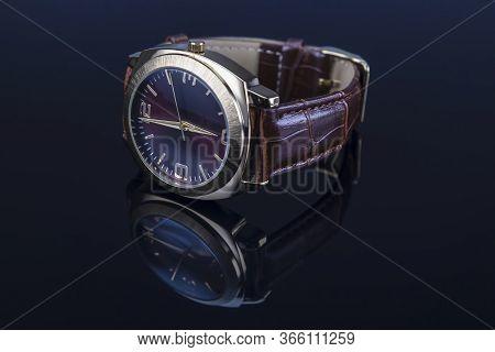 Men Wrist Watch With Leather Bracelet On Black Glossy Background.