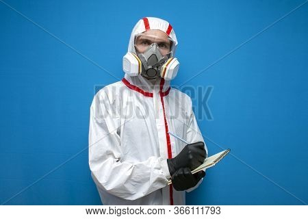 Disinfection Worker In Protective Suit And Respirator Writes Statistics, Virologist Doctor On A Blue