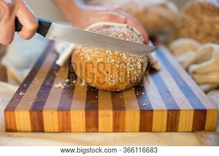 Baker Cutting Crusty French Loaf On Chopping Board. Closeup Shot, Bread In Background. Traditional B