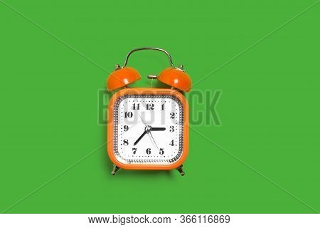 Vintage Style Orange Metal Alarm Clock With Bells Standing On The Green Background Isolated. Back To