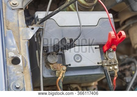 Car With Internal Combustion Engine. The Hood Is Open And The Battery Is Being Serviced.