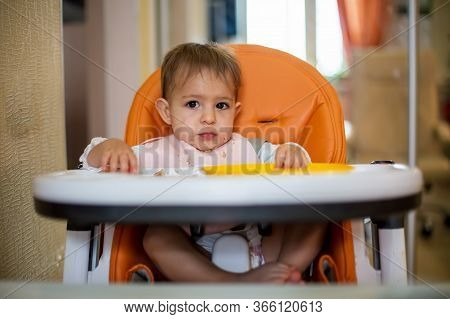 Cute Caucasian Baby Girl Sitting In An Orange Baby Chair After Eating With Crumbs On Her Face, On Th