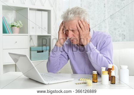 Portrait Of Sad Sick Senior Man Using Laptop