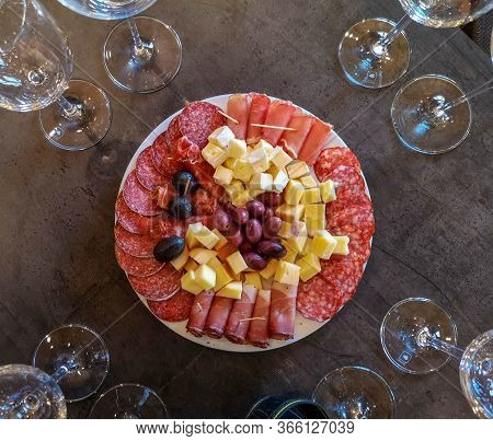 Top View Of A Table With Empty Glasses And A Plate With Various Cold Cuts: Sliced Ham, Bacon, Salami