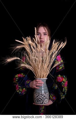 Woman In National Dress Holding A Bouquet Of Dry Wheat In A Vase. On Black Bakground. Face Covered W